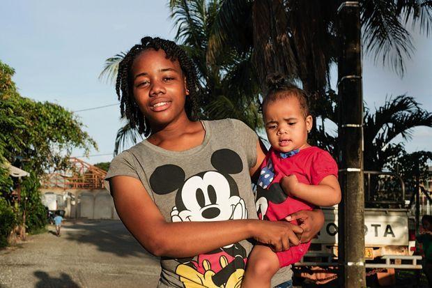 Shaïna, 16 ans, avec sa fille Claïna, 15 mois, dans les rues de Cayenne. Elle adore Mickey, mais sa passion c'est les maths.