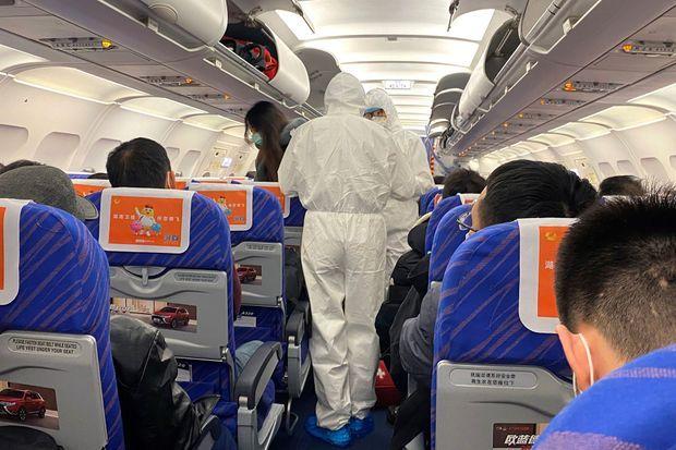 Contrôle d'un passager à bord d'un avion qui vient d'atterrir à Shanghai, en provenance de la province où l'essentiel des cas d'infections sont répertoriés, samedi.