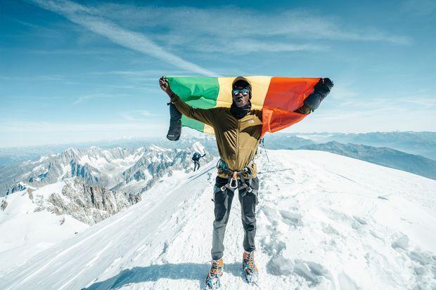 Sikou, en haut du Mont Blanc, pose avec le drapeau malien.