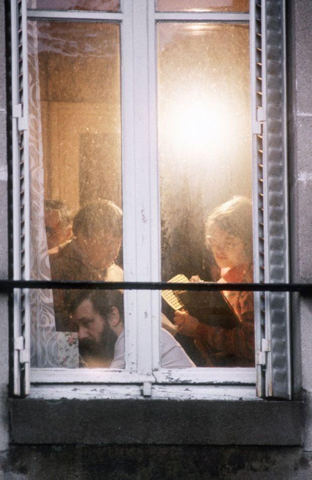 """Le juge Gilbert Thiel (en bas à gauche), chargé de l'instruction du dossier dans l'affaire du """"meurtre sans cadavre"""" à Nancy, assisté de sa greffière (D) et d'un policier (en haut à gauche) a perquisitionné, le 14 janvier 1986, au dernier domicile nancéen des soeurs Simone et Madeleine Weber."""