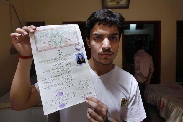 Hassan Khan brandissant le certificat de mariage.