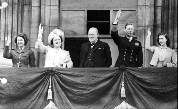 La princesse Elizabeth avec ses parents le roi George VI et la reine consort Elizabeth, sa sœur la princesse Margaret et le Premier ministre Winston Churchill, le 8 mai 1945