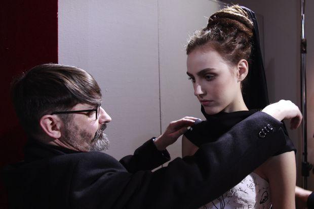 En 2011, Franck Sorbier ajuste la robe d'un mannequins, à quelques minutes du défilé.
