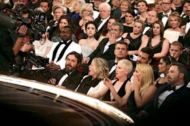 Stupéfaction dans la salle après le couac historique de l'Oscar du meilleur film. Au premier rang, on distingue Casey Affleck (meilleur acteur), Michelle Williams et Ben Affleck. Au deuxième rang, Mel Gibson, Matt Damon et Salma Hayek.