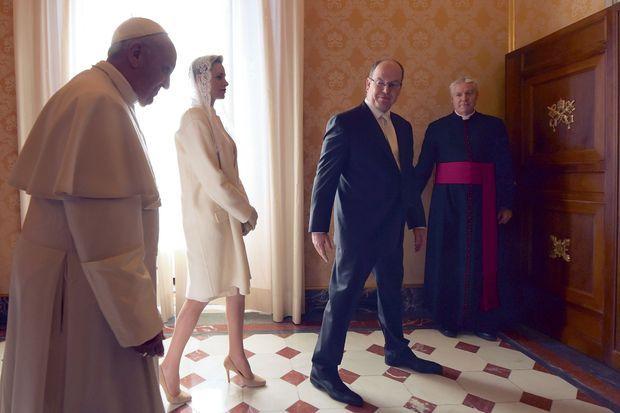 Sur le chemin du salon officiel, le Pape laisse passer le couple princier. Charlène porte une robe manteau signée Céline.