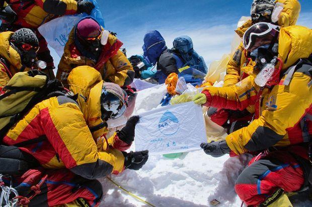 Sur le toit du monde, à 8849 mètres, des guides tibétains se photographient avec le logo Clean Everest pour promouvoir une meilleure gestion des déchets.