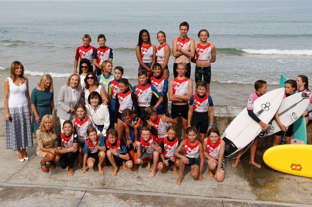Melania Trump, Malgorzata Tusk, Brigitte Macron, Cecilia Morel, Adele Malpass, Jenny Morrison et Akie Abe posent avec de jeunes surfeurs.