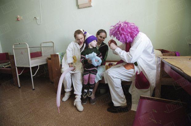 « Sur les genoux de sa mère, Oleg reçoit la visite des clowns Antocha et Assya. » - Paris Match n°2449, 2 mai 1996