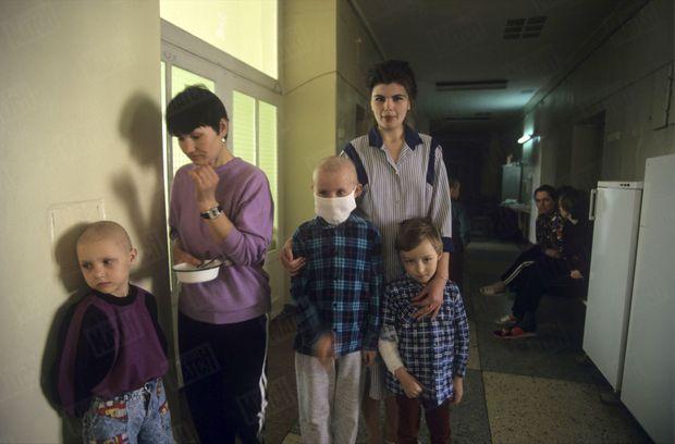 """« La thérapie des """"docteurs rêve"""" aide les petits leucémiques à surmonter l'épreuve. Pendant que sa mère essaie de faire manger un petit malade qui n'arrive pas à avaler (à g.), Angela, l'assistante sociale protège un autre garçon rendu chauve par la chimiothérapie et une petite fille au bras plâtré pour cause de déficit osseux. » - Paris Match n°2449, 2 mai 1996"""