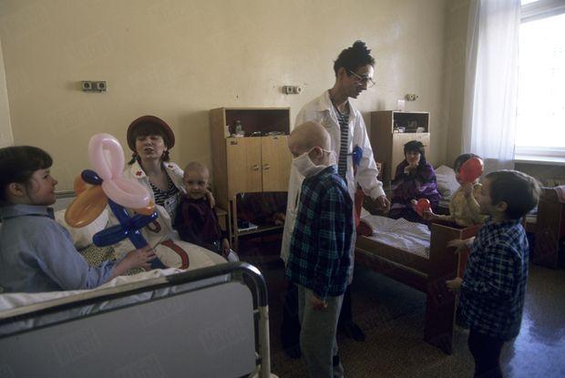 « A la souffrance s'ajoutent les problèmes dus à la crise économique : les hôpitaux, mal équipés, manquent de moyens. Les conditions d'asepsie ne sont pas toujours respectées. Faute de place, des enfants particulièrement sensibles aux infections ne peuvent pas être isolés. Ils sont entassés dans des chambres communes, et munis de masques censés les protéger. Le personnel de l'hôpital de Minsk doit faire face à une tâche impossible, et il sait que ceux qu'il va guérir retourneront en zone contaminée, comme les autres Russes, Biélorusses et Ukrainiens installés dans des secteurs qui auraient dû être évacués. Souvent, les mères des petits malades vivent avec eux à l'hôpital : c'est très important pour leur moral. Tout comme les visites des «docteurs rêve », ces clowns qui ne donnent de représentations qu'au chevet des jeunes hospitalisés. Ils officient à Minsk, mais aussi à Soweto, à Rio, au Japon et en Suisse - c'est dans ce dernier pays que Jean et André Poulie ont créé la fondation Théodora, du nom de leur mère, morte d'un cancer. » - Paris Match n°2449, 2 mai 1996