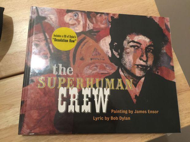 The Superhuman Crew, édité par le Getty Museum de Los Angeles. L'ouvrage, qu'Arno recherche au MuZee pour nous le montrer rassemble deux œuvres d'art visionnaires : L'entrée du Christ à Bruxelles en 1889 et le morceau Desolation Row de Bob Dylan, extrait de l'album Highway 61 Revisited (1965) .