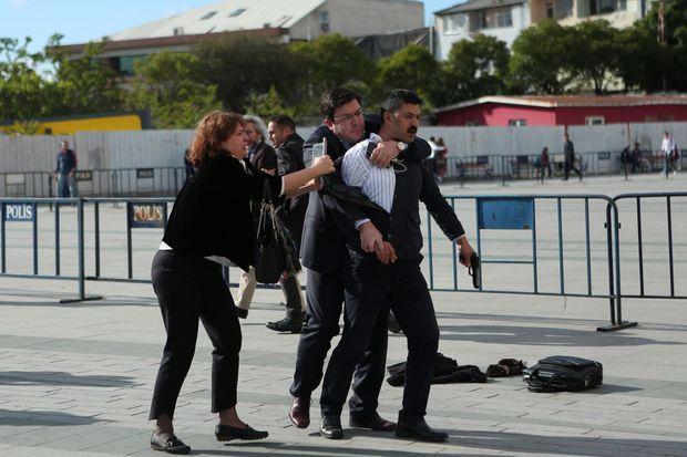 Un homme maîtrise le tireur, sous le regard de Dilek Dündar, tandis que le journaliste Can Dündar est emmené à l'écart.