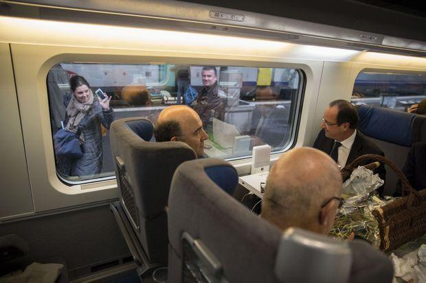 Vendredi 3 mai, gare de Besançon. Le président sourit à une passante qui l'a photographié. Avec Pierre Moscovici et Michel Sapin, il regagne Paris après la visite d'usines dans le Doubs. Sur la table, un panier gourmand ofert par la Chambre de commerce.