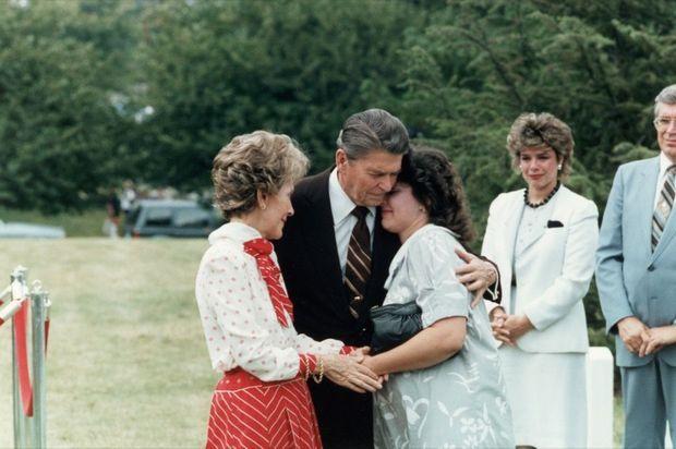 Le président américain Ronald Reagan et son épouse Nancy, réconfortant la soeur de Robert Stethem, lors d'une cérémonie au cimetière d'Arlington, en juillet 1985.