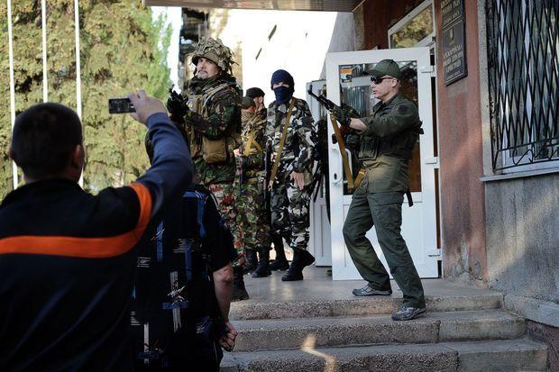"""Krasnoarmeisk, Ukraine. Le 11/05/14. A droite de l'image, Andreï Denisenko, l'un des chefs du groupe nationaliste Pravy Sektor, tire en l'air pour disperser la foule qui voulait participer au référendum séparatiste du Donbass. L'homme à sa gauche est identifié par des résidents comme un chef du """"Bataillon du Dniepr""""."""