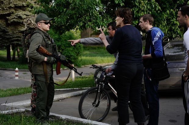 Des civils parlementent avec Andreï Denisenko, l'un des chefs du groupe nationaliste Pravy Sektor, a l'exterieur du batiment. En début d'après-midi, des hommes armés d'appartenance ukrainienne ont empeché le vote du référendum et occupé le batiment administratif de la petite ville de Krasnoarmiysk.