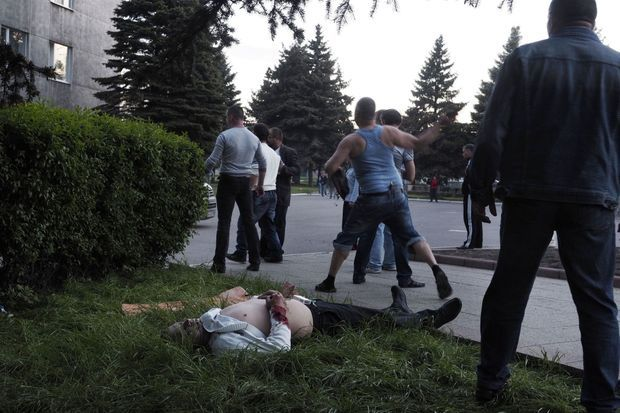 Youri Nikolenko, 48 ans, au centre, en tee-shirt bleu, jette une pierre au moment où les miliciens se replient dans leurs camionnettes.