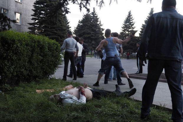 Youri Nikolenko throws a stone at the gunmen.