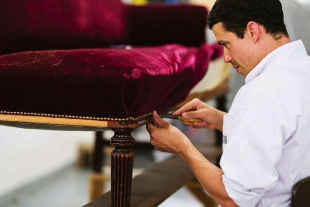 Un artisan de l'atelier Phelippeau Tapissier pose des clous décoratifs sur une banquette