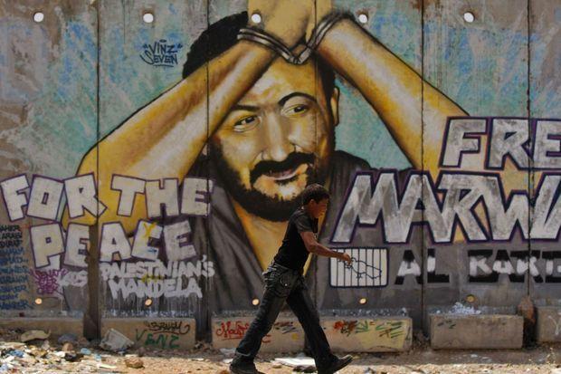 Un enfant passe près d'un mur peint, représentant Marwan Barghouti.