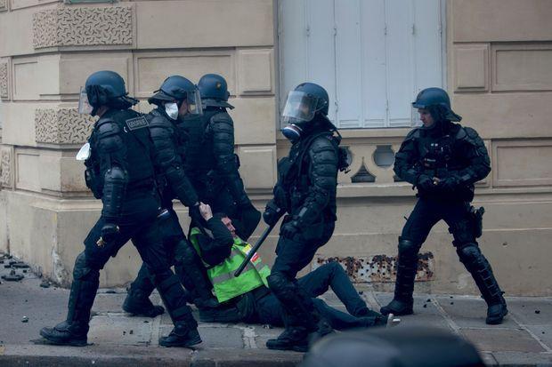 A l'angle de l'avenue Marceau et de la rue Galilée, 15 h 51. Un gilet jaune est traîné avec vigueur.