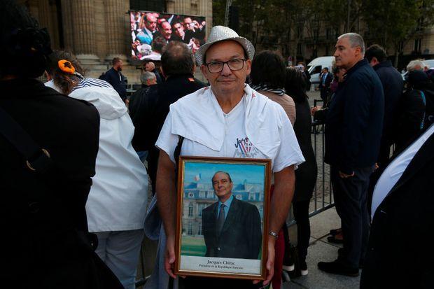 Un homme pose avec un portrait du président Chirac devant l'église Saint-Sulpice, à Paris, lundi.