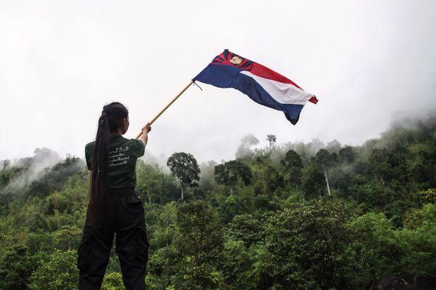 Une rebelle brandit le drapeau du Kaw Thoo Lei, l'État libre et indépendant karen.