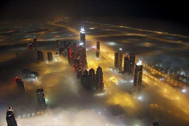 Une vue onirique des tours de Dubai embrumé percé de mille feux, photographié par le cordiste Pascal Beteille.
