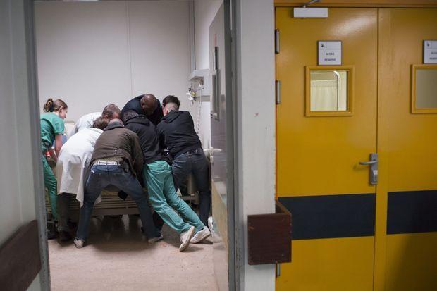 Une prime de risque de 70 centimes à 4 euros... dans le box 5, trois infirmiers (en vert), deux médecins dont un psychiatre (en blanc), un vigile et deux policiers immobilisent un patient.