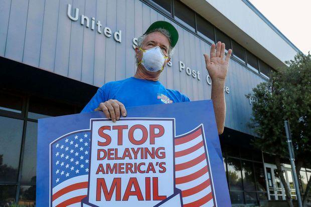"""Un employé de l'USPS, la poste américaine, manifeste le 25 août à Pasadena en Californie pour dénoncer les réformes imposées à ce service public juste avant la présidentielle. Sur la pancarte : """"Arrêtez de retarder le courrier de l'Amérique""""."""