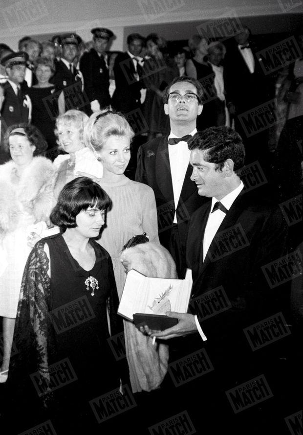 """Agnès Varda et Jacques Demy au 17ème Festival de Cannes, en 1964, avec la Palme d'or que le réalisateur vient de recevoir pour son film """"Les parapluies de Cherbourg"""". Derrière eux, Michel Legrand, compositeur de la musique, et son épouse Christine."""
