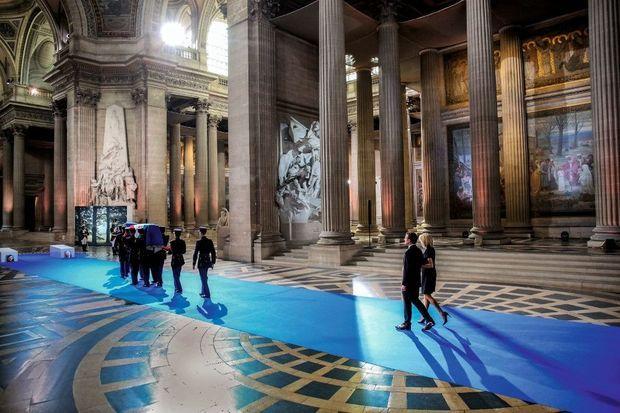 Les gardes républicains portent les cercueils, suivis d'Emmanuel et Brigitte Macron.