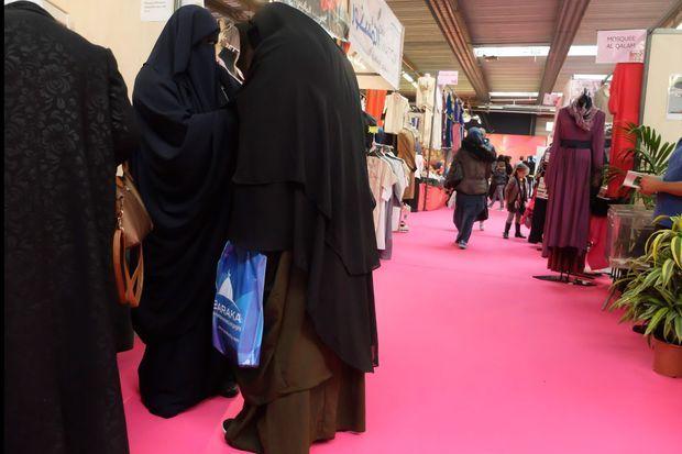 Des femmes entièrement voilées font leur shopping dans le Salon où des stands proposent des niqabs dernière tendance.