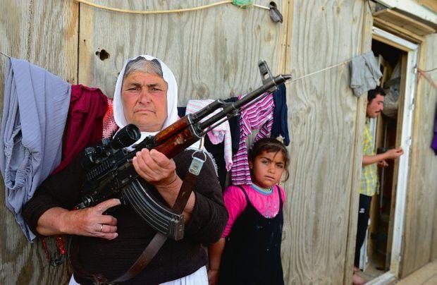 Hitte (à g.) devant l'ex-baraquement construit par les Américains sur les monts Sinjar, où elle s'est réfugiée avec sa famille.
