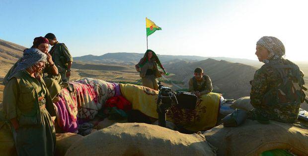 Deux hommes viennent ravitailler un groupe isolé de combattantes. De g. à dr. : Zilan, Dijla, Sila et Suzdar. A l'horizon, les positions de Daech.