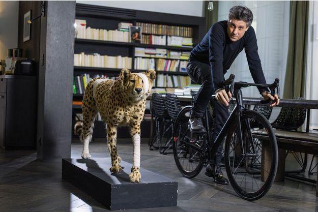 Chez lui, à Paris, sur un vélo fabriqué par sa société Heroïn. A sa droite, un des «Accidents de chasse» du plasticien Pascal Bernier, pour alerter sur la fragilité de l'environnement