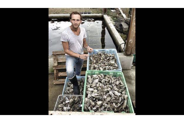 Julien Brizard, photographié dans la claire de sa cabane à Andernos-les-Bains devant des cageots d'huîtres mortes.