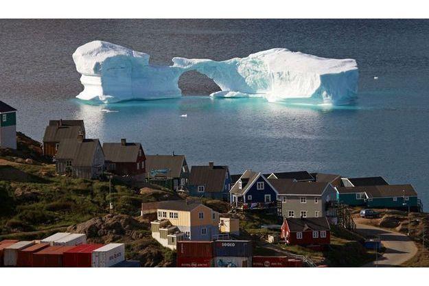 Un iceberg dérive devant la ville de Kulusuk au Groenland. Cette région du monde sert aux scientifiques de repère pour mesurer les effets sur le climat.