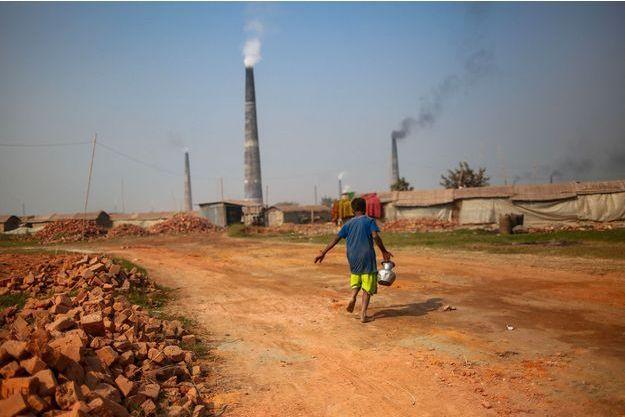 Au Bangladesh, un enfant porte une cruche d'eau devant des centrales.