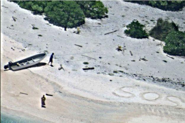 Le SOS des naufragés écrit sur le sable.
