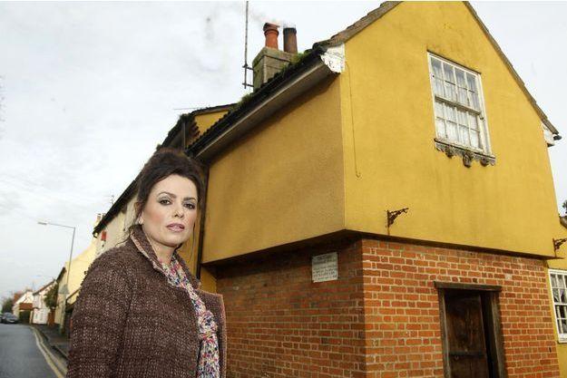 """Vanessa Mitchell devant """"The Cage"""", sa maison hantée désormais à vendre."""