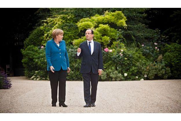 Le 27 juin 2012, dans les jardins de l'Elysée. Angela Merkel et François Hollande s'entretiennent avant la rencontre européenne de Bruxelles des 28 et 29 juin, énième « sommet de la dernière chance » pour sauver la zone euro.
