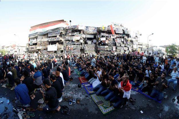 Des personnes se sont rassemblées près de ce bâtiment ravagé par l'attentat pour prier. Sur ce quil reste de sa façade, des drapeaux, des portraits des victimes et des messages ont été accrochés