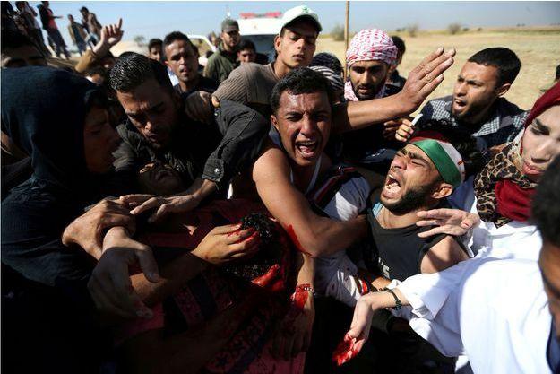 Des Palestiniens transportent un jeune homme de 17 ans blessé à la tête à Gaza.