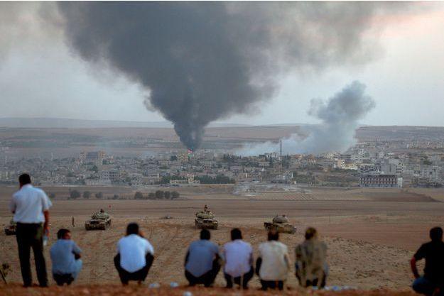 Le 9octobre 2014, près de Suruç, à la frontière  turco-syrienne. Derrière les chars turcs immobiles, des Kurdes, témoins impuissants de la bataille de Kobané.