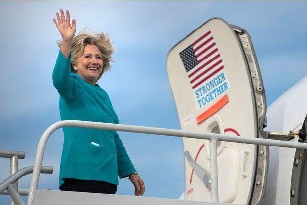 Hillary Clinton souriante avant de prendre son avion de campagne.