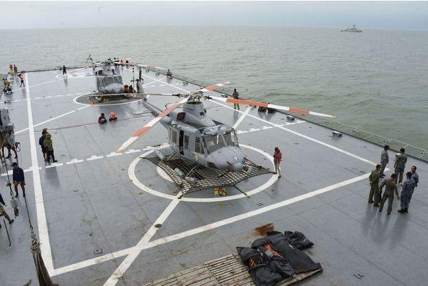 """Sur le pont du """"KRI Banda Aceh"""", un navire de la marine indonésienne qui participe aux recherches. Les hélicoptères servent à transporter les corps retrouvés en mer et placés dans des sacs mortuaires."""