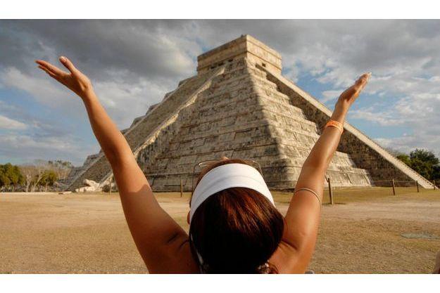 Une jeune femme capte l'énergie du soleil devant la pyramide maya d'El Castillo, sur le site de Chichen Itza, au Mexique.