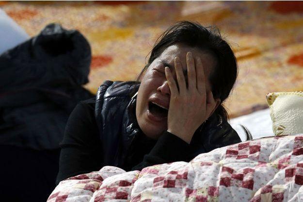 Une proche de l'une des victimes pleure.