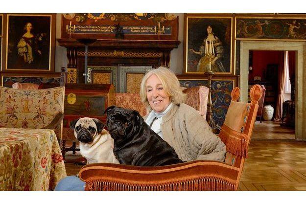 Diana Phipps Sternberg pose,  avec ses carlins, sous les armoiries de sa famille. En 1992, elle s'est engagée  dans la restauration de son château  de Castolovice, en Bohême. C'est toute l'histoire de ses aïeux qui a repris vie.